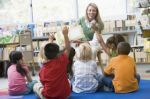 Children listening to a librarian read a book for storytime